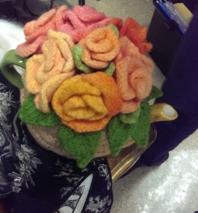 Tea cozy topped with knit flowers, which were hand painted with Kool-aid, just as one would marzipan.